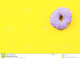 purple round donut on yellow background flat lay top view stock