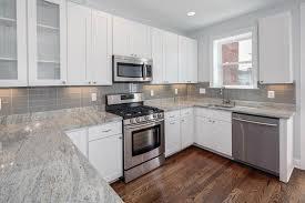 smoke gray glass subway tile backsplash in bright kitchen design
