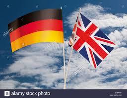 Germman Flag English Flag And German Flag Against Cloudy Sky Stock Photo