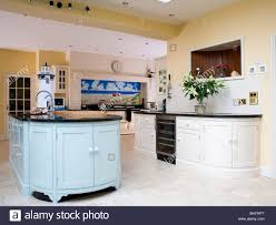 pastel blue island unit in large pale yellow kitchen extension