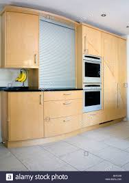 pale wood fitted kitchen cupboards and units with large tambour