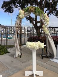 rustic wedding arch draped fabric and fresh flowers white and