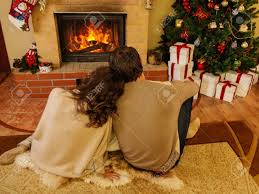 Decoration House by Couple Near Fireplace In Christmas Decorated House Interior Stock