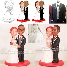 black cake toppers and groom touching wedding cake toppers
