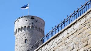 Estonian Flag Round Tower With Estonian Flag And Part Of Wall With Iron Fence