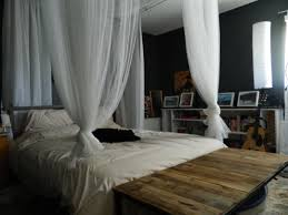 bedroom white canopy bed drapes with table and grey wall for