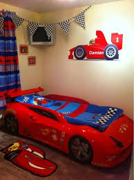 kids bedroom with red race car bed and white nightstand car bed
