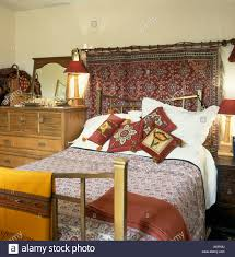 indian wall hanging above brass bed with patterned red cushions