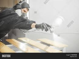 ventilation mask for painting man in respirator mask painting wooden planks at workshop male