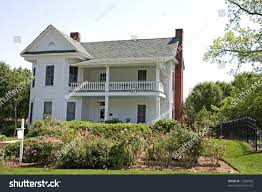 white traditional colonial house behind rose stock photo 13305958
