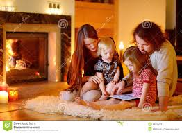 happy family using a tablet pc by a fireplace stock image image