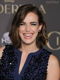elizabeth henstridge wearing a blue dress with black sequins her hair in wavy bob prom makeup