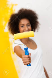 african american woman with a paint roller covered in bright