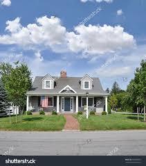 suburban home cape style architecture american flag landscaped