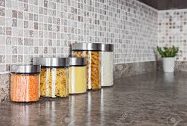 glass kitchen canisters food ingredients in glass jars on a kitchen counter top stock