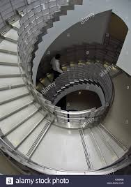 view from above of man walking up circular staircase in hospital