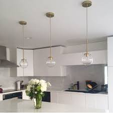 modern kitchen using clear glass pendants hung over island l