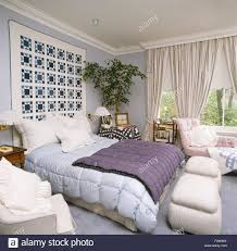 patchwork quilt on wall above bed with pale blue and purple quilts