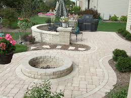 exterior backyard patio ideas with white pavers and round fire