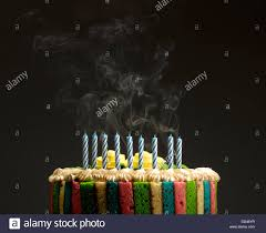 a colorful birthday cake with blown out candles and smoke stock