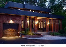 Twilight House Front Of A Red Brick House At Twilight With Pond Pillars And Stone