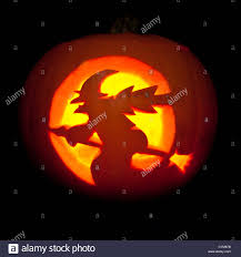 witch on a broomstick carved halloween pumpkin lantern stock photo