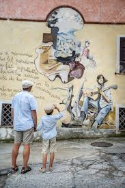 happy father and son walking outdoors in village orgosolo italy happy father and son walking outdoors in village orgosolo italy murals wall paintings about