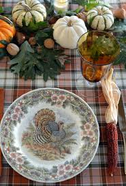 a thanksgiving table with turkey plates plaid and pumpkin oak