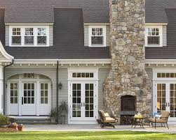 outdoor stone fireplace and chimney on a traditional gray shingled