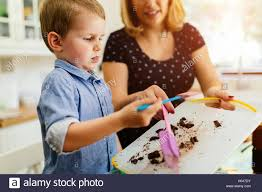 smart cute child helping mother in kitchen preparing cookies stock