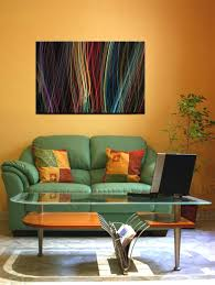 sage green couch with abstract picture and orange wall color for