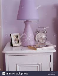 close up of alarm clock and mauve lamp on white bedside cabinet in close up of alarm clock and mauve lamp on white bedside cabinet in mauve bedroom