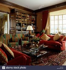 A Study With Walls In by Sofa And Armchairs Around Coffee Table In Book Lined Study With