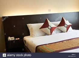 double bed setting with bed runner and decorated cushions stock
