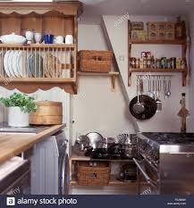 pine plate rack above worktop in a cottage kitchen with stainless