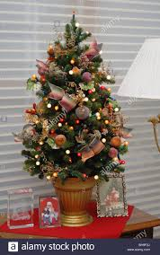 a small elegantly decorated tree sits atop a table in a