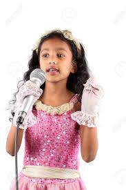 a little indian singing with a mic on white studio