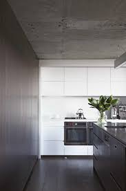 kitchen concrete ceiling white handleless cabinets white stone