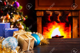 christmas decorations a gift and candles in front of a fireplace christmas decorations a gift and candles in front of a fireplace a fire is