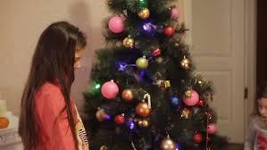 a woman decorates a small christmas tree in a house stock footage