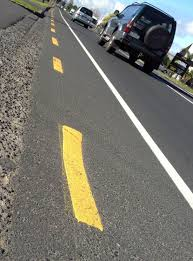 a broken yellow line painted close to the edge of the road means