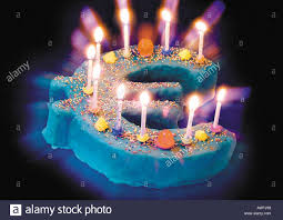 euro sign birthday cake with ten candles burning on top stock