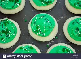 green frosted sugar cookies with shamrock sprinkles stock photo