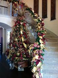 burgundy and gold tree against the staircase with