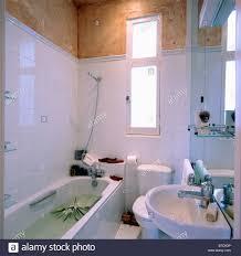 shower above bath in modern white tiled bathroom stock photo