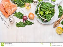 salmon with spinach cooking preparation on white wooden kitchen