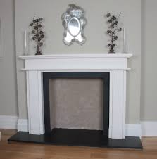 white fireplace surround with shelf above also black fireplace on