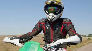 motocross protection gear motocross racer in motorcycle gear riding bike on rural road