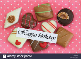happy birthday card with selection of chocolates on pink