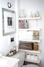 white wooden shelves on white wall near white wooden toilet bowl